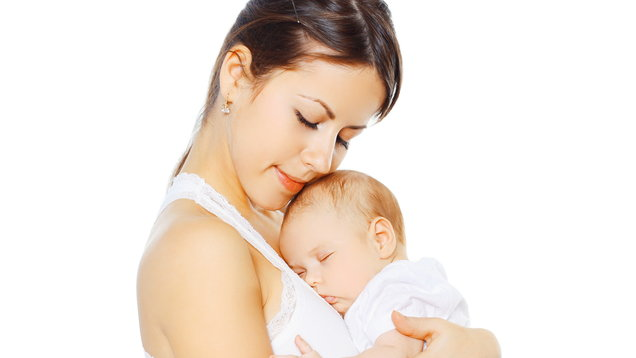 Portrait loving mother kissing her baby on a white background