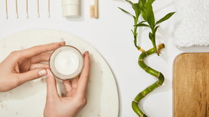 cropped view of woman holding cosmetic cream over marble round board, toothbrush, toothpaste in tube, ear sticks, bamboo stem and towel on white background