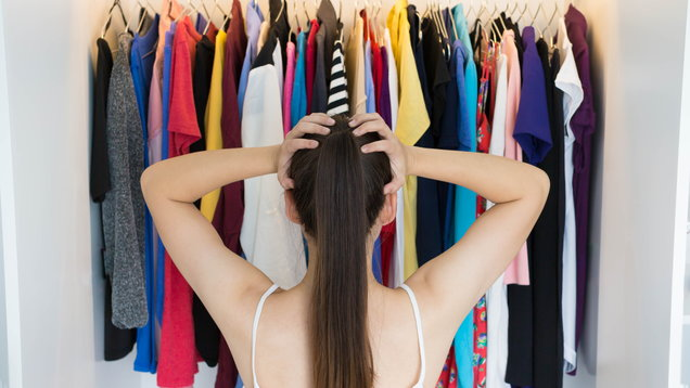 Confused woman choosing what to wear in front of her wardrobe