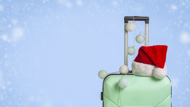Plastic suitcase, Santa Claus cap and garland on a blue background with snow. Concept of travel, business trips, trips to visit friends and relatives on Christmas holidays. New Year's journey.