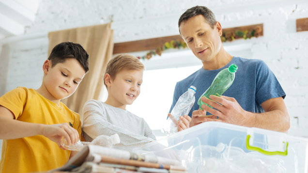 Father and sons preparing plastic bottles for recycling