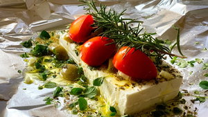 Feta cheese on aluminum foil with rosemary, garlic,olives, thyme and tomatoes