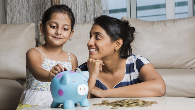 Mother and daughter putting coins into piggy bank – Stock image